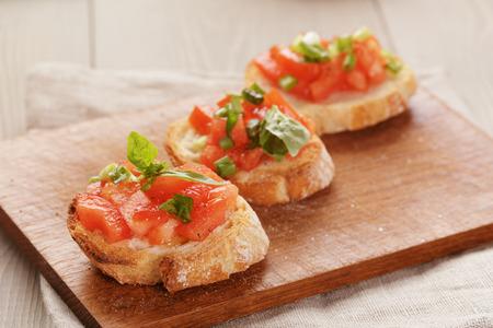 간단한 이탈리아어 식욕을 돋 우는 브루 쉐 타 토마토와 바 질, 오래 된 테이블