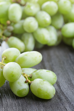 ripe green grapes on black wood table photo
