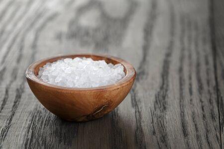 salt: la sal del mar en un taz�n de madera para la cocina o el balneario, en la mesa oscura