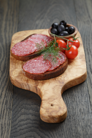air dried salami: rye bread with salami on olive board Stock Photo