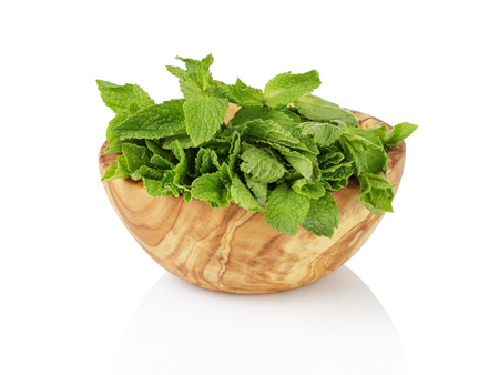 overwhite: bunch of fresh spearmint in wood bowl isolated on white Stock Photo