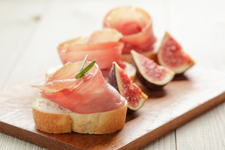 canapes with jamon and figs on wooden board, soft light photo