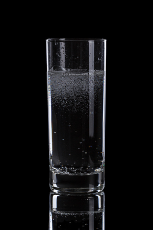 highball: mineral water in simple highball glass, on black background Stock Photo