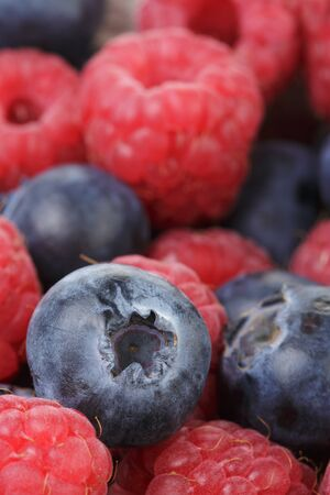 close up photo of ripe  blueberry and raspberry, organic berries