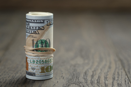 roll of new style hundred dollar bills stand on wooden table photo