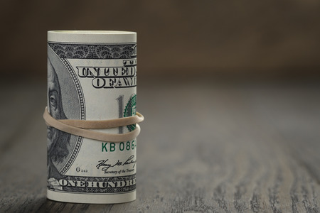 dolar: rollo de estilo billetes de cien dólares de edad de pie en la mesa de madera Foto de archivo