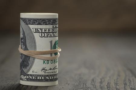 rouleau de vieux style de billets de cent dollars debout sur la table en bois