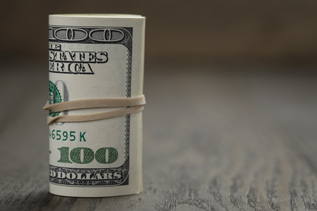 roll of old style hundred dollar bills stand on wooden table photo
