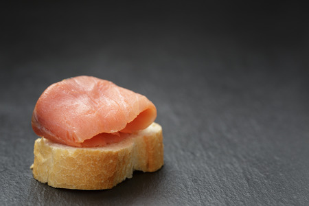 baguette slice with curred salmon on slate background photo