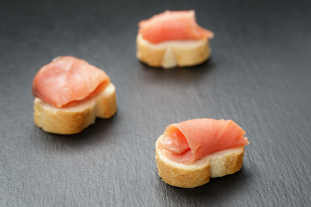 baguette slices with curred salmon on slate background photo