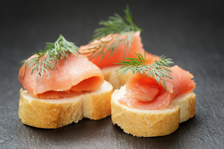 baguette slices with curred salmon and dill on slate background photo