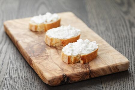 crunchy baguette slices with cream cheese on olive board Standard-Bild