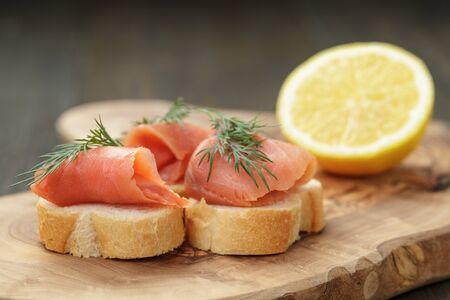 baguette slices with curred salmon and dill on wood table photo