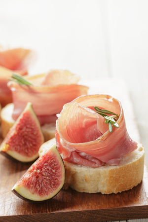 canapes with jamon and figs on wooden board photo