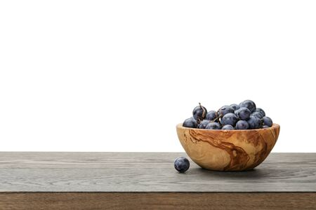 isabella grapes in wood bowl on table, border compostition photo