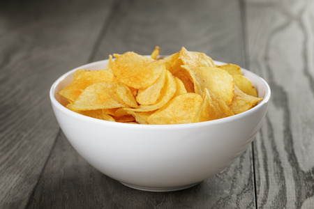 potato chip: organic potato chips in white bowl on wood table