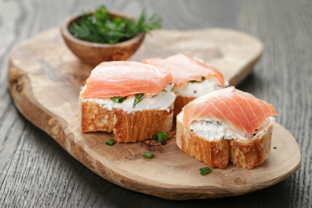 baguette slices with smoked salmon and cheese cream on wooden table Stockfoto