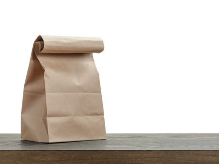 paper craft: simple de la bolsa de papel marrón para el almuerzo o la comida en la mesa de madera Foto de archivo