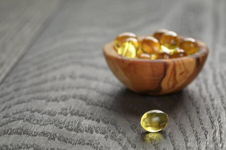 eating fish: fish oil capsules in wood bowl on wooden table