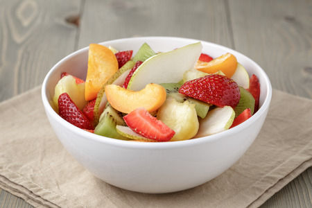 fresh mix fruit salad with strawberry, kiwi and peach, on table photo