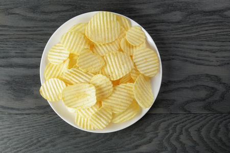 rippled potato chips in white plate on wood table Stockfoto