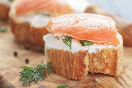small sandwiches with soft cheese and salmon on wood table photo