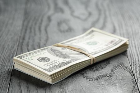 mazzo di banconote da cento dollari legato con elastico sul tavolo di legno
