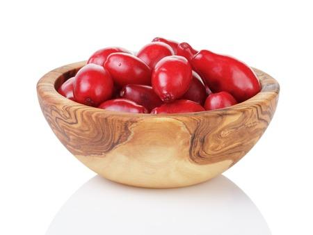 burgundy colour: fresh bogwood berries in wood bowl isolated on white