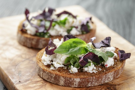 rustic food: rye sandwich or bruschetta with ricotta, herbs and basil