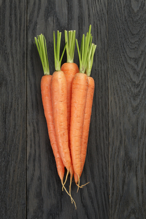 fresh carrots on old oak table top view Stockfoto