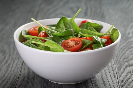 light breakfast: fresh summer organic salad with tomatoes cucumbers and spinach
