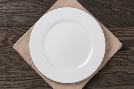 냅킨 나무 테이블에 빈 흰색 접시, 상위 뷰