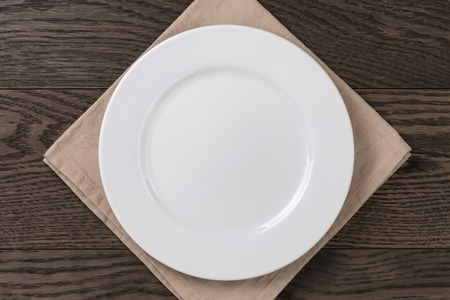 empty white plate on wood table with napkin, top view