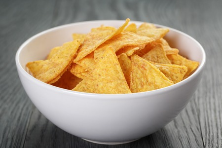 tortilla chips: tortilla chips in white bowl on wooden table, selective focus Stock Photo