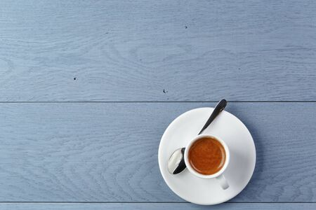 crema: cup of fresh espresso on vintage blue table from above