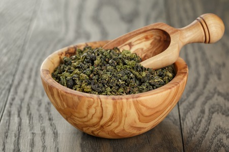 leaves green: oolong green tea in wood bowl, on oak table Stock Photo