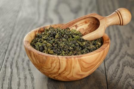 oolong green tea in wood bowl, on oak table Stockfoto