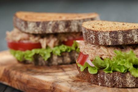 bocadillo: foto del primer de s�ndwich de at�n y verduras en el pan de centeno en el fondo de madera