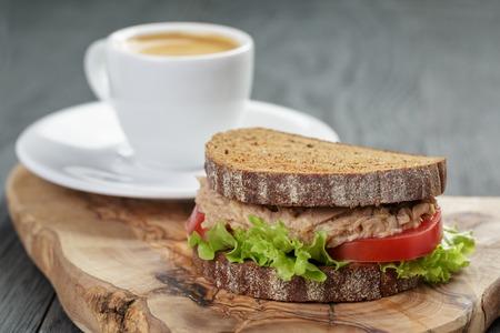 granos de cafe: espresso y un s�ndwich de at�n para el desayuno o el almuerzo en el fondo de madera Foto de archivo