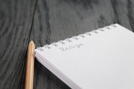 closeup photo of open notepad with word recipe, on wood table Stock Photo