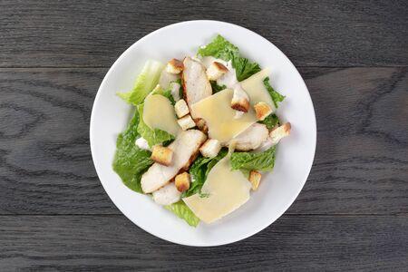 ensalada cesar: ensalada césar con pollo en la mesa de roble, comida mediterránea Foto de archivo
