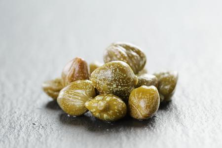 alcaparras: alcaparras marinados en un taz�n de oliva a bordo de pizarra, foco superficial