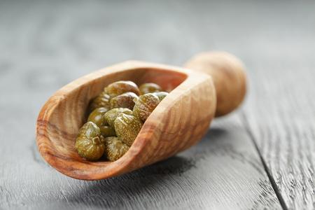 alcaparras: alcaparras marinados en primicia de madera en la mesa, foco superficial Foto de archivo