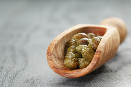 alcaparras: marinated capers in wood scoop on table, shallow focus Foto de archivo