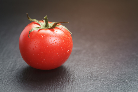 ripe tomato on slate board, vintage toned