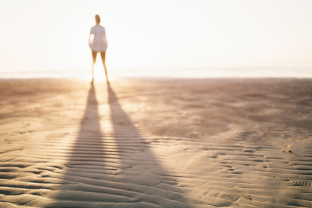 defocused photo of girl standing on beach, long shadow Standard-Bild