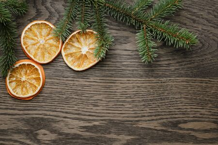 spruce tree: spruce twig with dried orange slices on oak table, christmas background