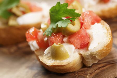 olive green: homemade crostini with tomato, mozzarella and olives on wooden table