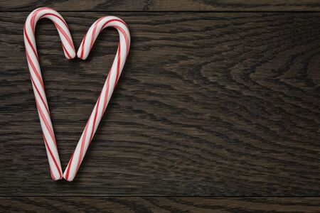 christamas: heart from candy canes on wooden table, romantic christmas background Stock Photo