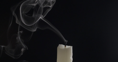 burned out: one candle with smoke trail on dark background